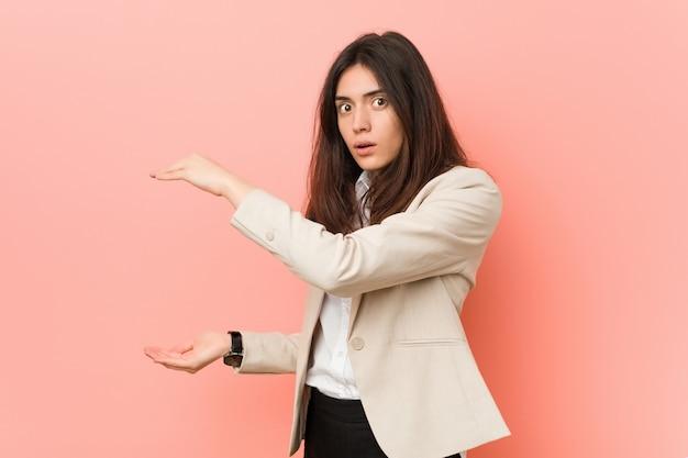 Junge brunettegeschäftsfrau gegen einen rosa hintergrund entsetzt und überrascht, einen kopienraum zwischen händen halten.