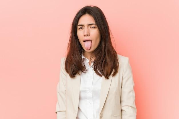 Junge brunettegeschäftsfrau gegen einen rosa hintergrund lustig und freundlich, zunge heraus haftend.