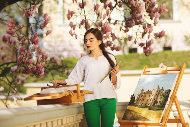 Junge brunettekünstlerin, die in den händen eine bürste und eine palette hält. in der nähe ihrer staffelei, gemälden und verschiedenen kunstgeräten