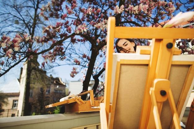 Junge brunettekünstlerin malt ein bild nahe dem magnolienbaum.