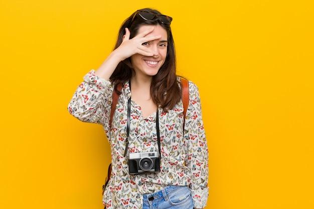 Junge brunettereisendfrau blinken an durch finger, verlegenes bedeckungsgesicht.