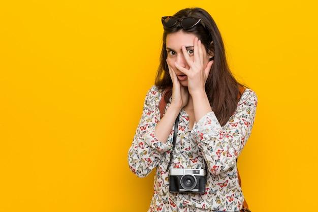 Junge brunettereisendfrau blinken durch die finger, die erschrocken und nervös sind.