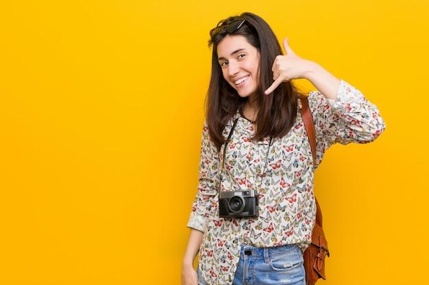 Junge brunettereisendfrau, die eine handyanrufgeste mit den fingern zeigt