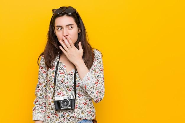 Junge brunettereisendfrau, die eine müde gestenbedeckungsmund mit der hand zeigend gähnt.