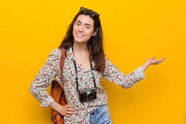 Junge brunettereisendfrau, die einen kopienraum auf einer palme zeigt und eine andere hand auf taille hält.