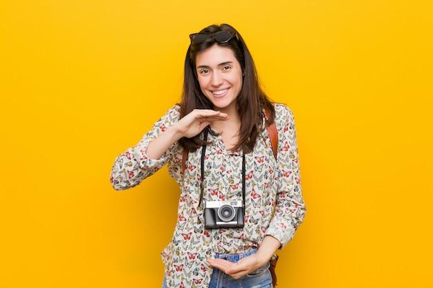 Junge brunettereisendfrau, die etwas mit beiden händen, produktdarstellung hält.