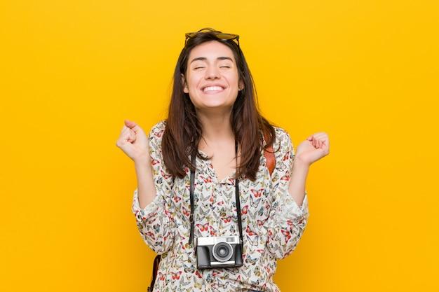 Junge brunettereisendfrau, die faust anhebt, glücklich und erfolgreich sich fühlt