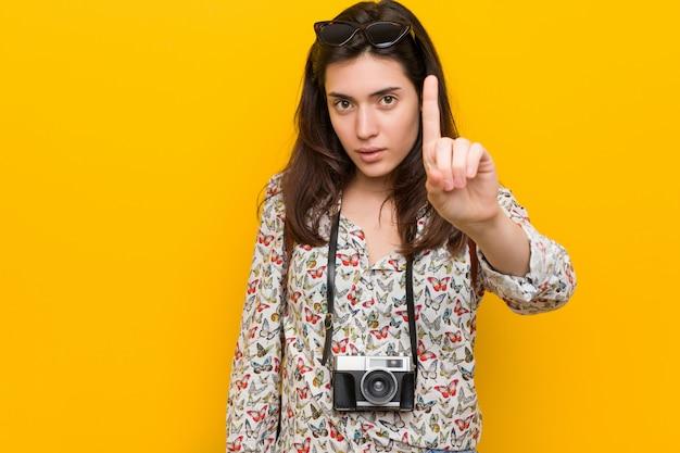 Junge brunettereisendfrau, die nummer eins mit dem finger zeigt