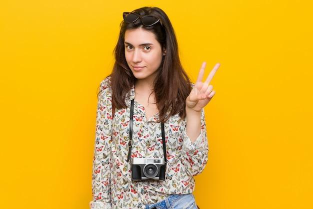 Junge brunettereisendfrau, die nummer zwei mit den fingern zeigt.