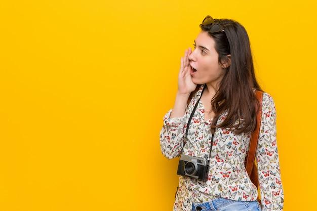 Junge brunettereisendfrau, die palme nahe geöffnetem mund schreit und hält.