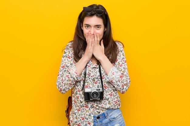 Junge brunettereisendfrau, die über etwas, mund mit den händen bedeckend lacht