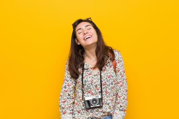 Junge brunettereisendfrau entspannte sich und glückliches lachen, der ausgedehnte hals, der zähne zeigt.