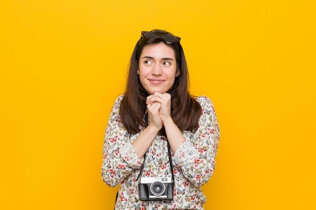Junge brunettereisendfrau hält hände unter kinn, schaut glücklich beiseite.