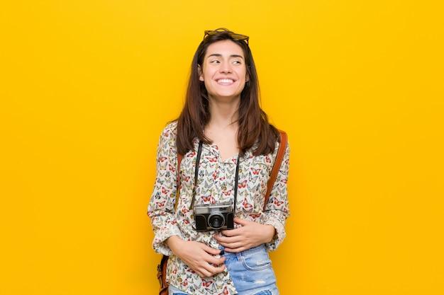 Junge brunettereisendfrau lacht glücklich und hat spaß, hände auf magen zu halten.
