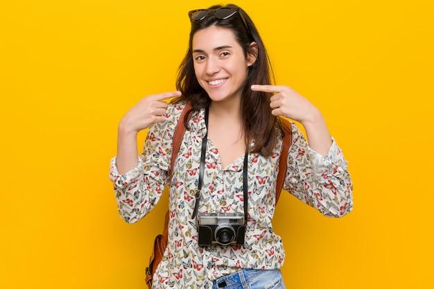 Junge brunettereisendfrau lächelt und zeigt finger auf mund.