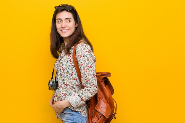 Junge brunettereisendfrau schaut beiseite lächelnd, nett und angenehm.