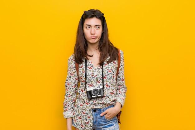 Junge brunettereisendfrau unglücklich, mit sarkastischem ausdruck in camera schauend.