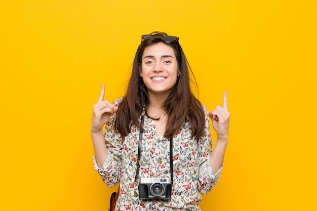 Junge brunettereisendfrau zeigt mit beiden vorderen fingern an, die sich eine leerstelle zeigen.
