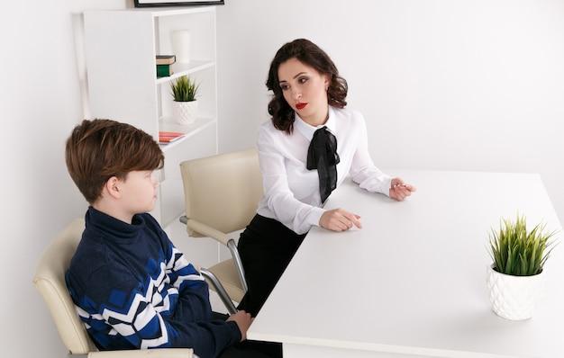 Junge brunnettefrau, die mit dem jungen drinnen den weißen raum spricht. psychologin mit patientin. psychologische therapie.