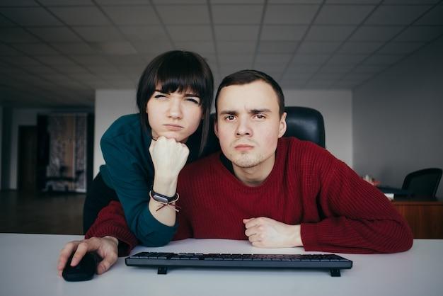 Junge büroangestellte, die am arbeitsplatz genau in die kamera schauen. emotional schöne junge leute am arbeitsplatz.