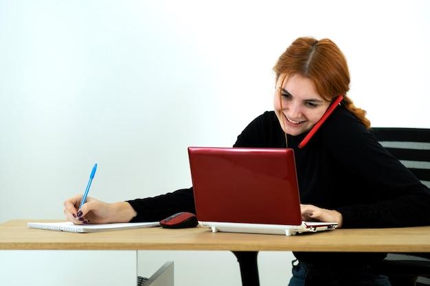 Junge büroangestelltefrau, die an einem handy spricht, das hinter schreibtisch mit laptop-computer und notebook sitzt.