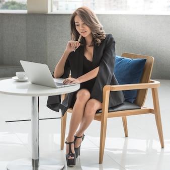 Junge bürogeschäftsfrau, die auf dem stuhl arbeitet an laptop sitzt