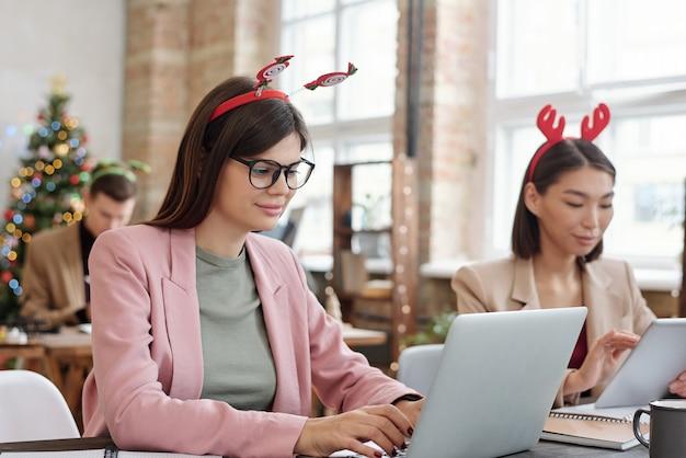 Junge büroleiterin in brillen und weihnachtskopfbedeckungen vernetzen sich vor dem laptop am schreibtisch gegen ihre kollegen mit gadgets