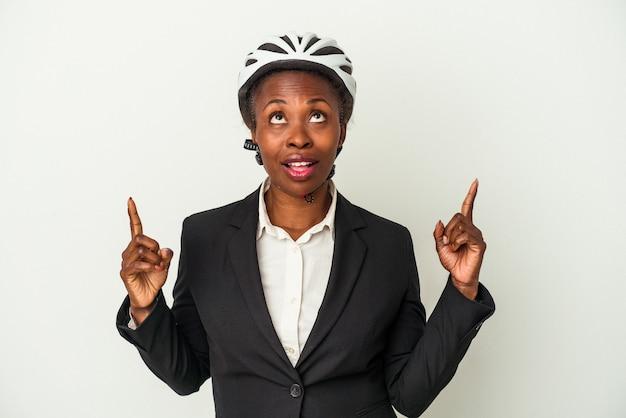 Junge business-afroamerikanerin trägt einen fahrradhelm isoliert auf weißem hintergrund zeigt nach oben mit geöffnetem mund.