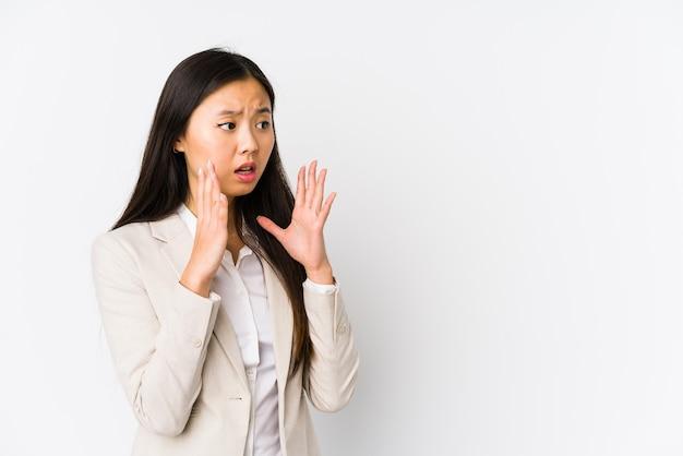 Junge business chinesische frau isoliert schreit laut, hält die augen offen und die hände angespannt.