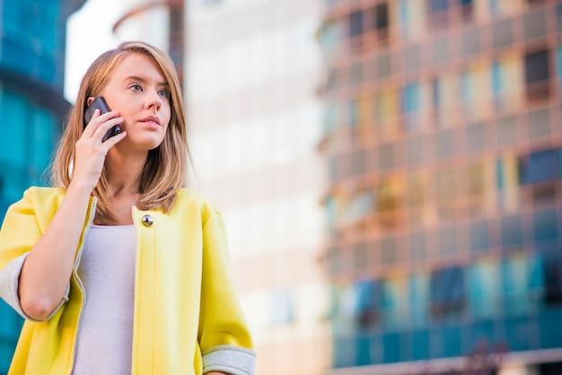 Junge business-frau macht einen anruf auf ihrem smartphone