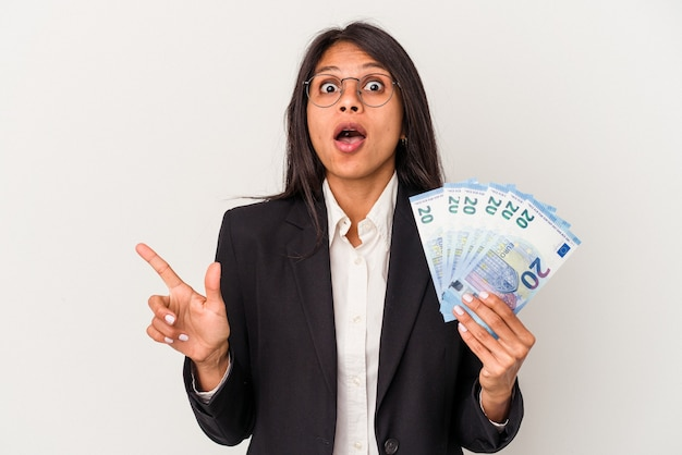 Junge business-latein-frau mit geldscheinen isoliert auf weißem hintergrund, die auf die seite zeigen