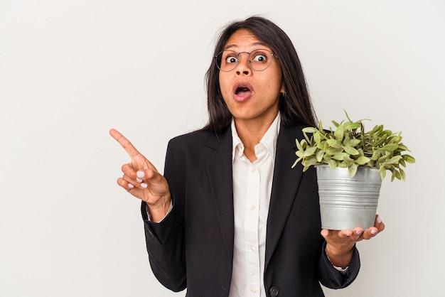 Junge business-latein-frau mit pflanzen isoliert auf weißem hintergrund zur seite zeigen