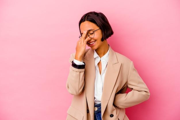 Junge business-mischlinge, die auf rosafarbenem hintergrund isoliert sind, blinken mit den fingern in die kamera, verlegen das gesicht.