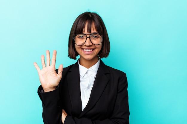Junge business-mixed-race-frau auf blauem hintergrund isoliert lächelnd fröhlich zeigt nummer fünf mit den fingern.