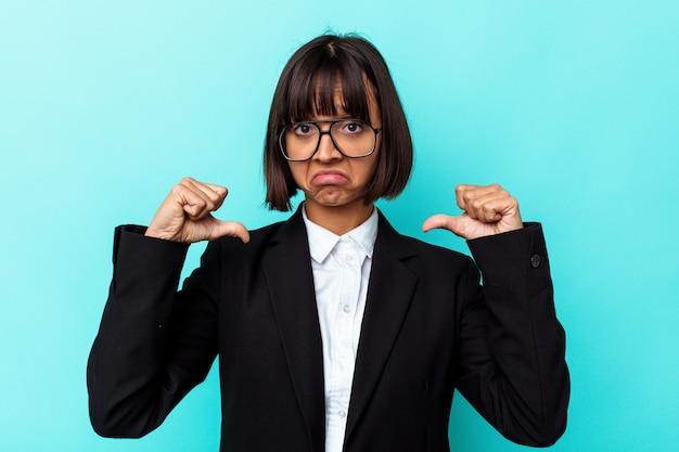 Junge business-mixed-race-frau, die auf blauem hintergrund isoliert ist, fühlt sich stolz und selbstbewusst, beispiel zu folgen.