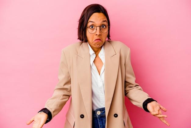 Junge business-mixed-race-frau, die auf rosafarbenem hintergrund isoliert ist, zuckt die schultern und öffnet die augen verwirrt.