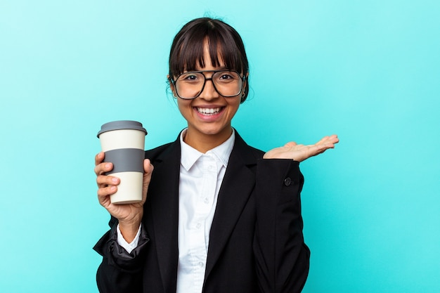 Junge business-mixed-race-frau, die einen kaffee auf blauem hintergrund hält, der einen kopienraum auf einer handfläche zeigt und eine andere hand auf der taille hält.