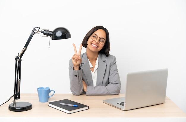 Junge business-mixed-race-frau, die im büro arbeitet, lächelt und zeigt siegeszeichen
