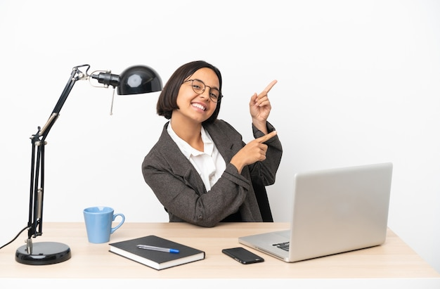 Junge business-mixed-race-frau, die im büro arbeitet, mit dem finger auf die seite zeigt und ein produkt präsentiert