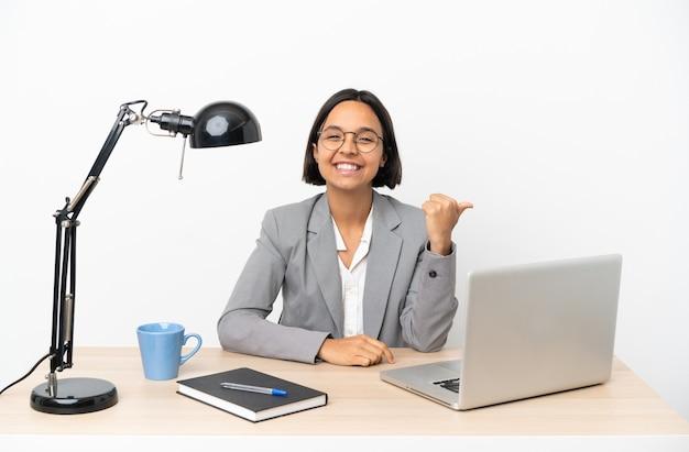 Junge business-mixed-race-frau, die im büro arbeitet und auf die seite zeigt, um ein produkt zu präsentieren