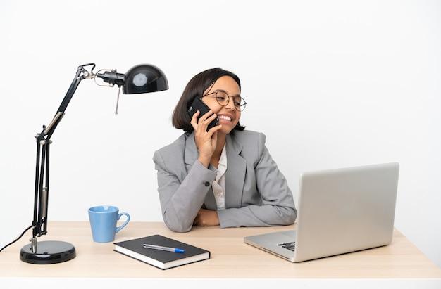 Junge business-mixed-race-frau, die im büro arbeitet und ein gespräch mit dem handy führt
