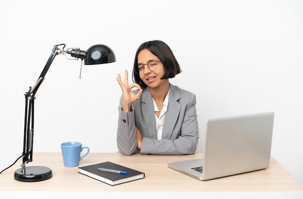 Junge business-mixed-race-frau, die im büro arbeitet und ein ok-zeichen mit den fingern zeigt
