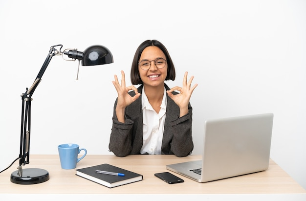 Junge business-mixed-race-frau, die im büro arbeitet und ein okay-zeichen mit zwei händen zeigt