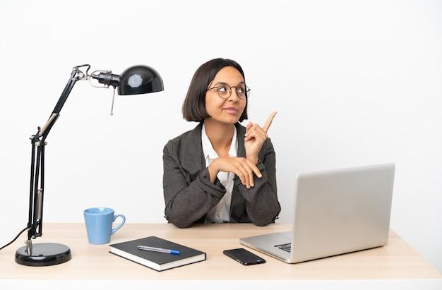 Junge business-mixed-race-frau, die im büro arbeitet und eine großartige idee aufzeigt