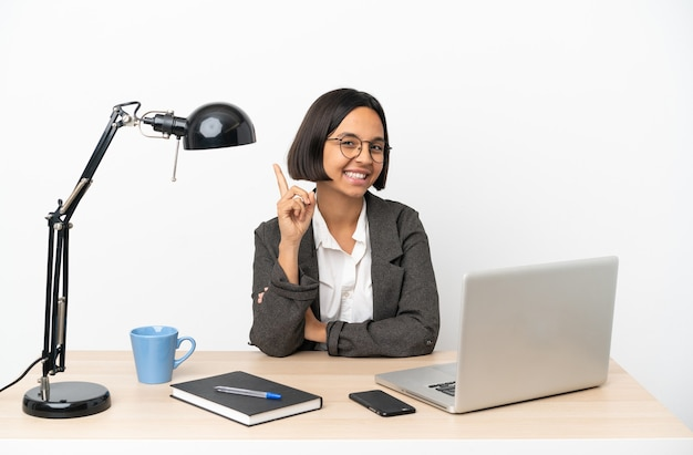 Junge business-mixed-race-frau, die im büro arbeitet und einen finger im zeichen des besten zeigt und hebt