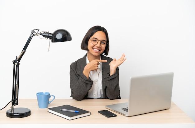 Junge business-mixed-race-frau, die im büro arbeitet und kopienraum imaginär auf der handfläche hält, um eine anzeige einzufügen?