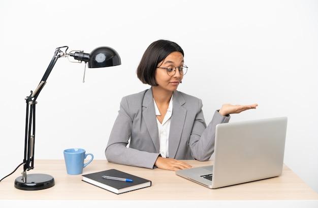 Junge business-mixed-race-frau, die im büro arbeitet und kopienraum mit zweifeln hält?