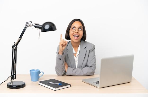 Junge business-mixed-race-frau, die im büro arbeitet und nach oben zeigt und überrascht