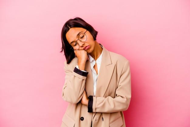 Junge business-mixed-race-frau einzeln auf rosafarbenem hintergrund, die gelangweilt, müde ist und einen entspannten tag braucht.