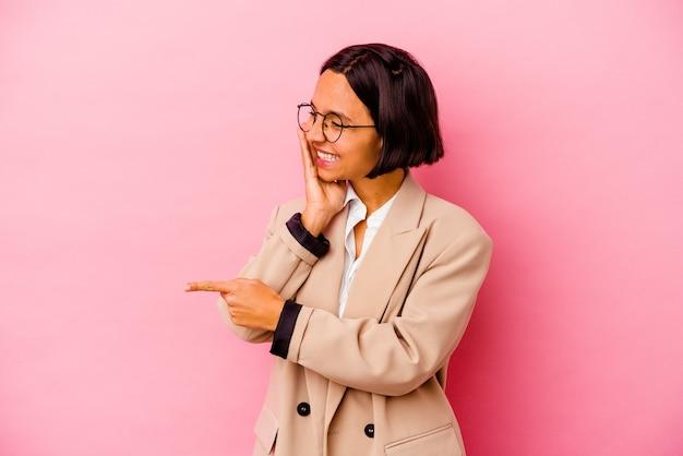 Junge business-mixed-race-frau isoliert auf rosa hintergrund, die einen klatsch sagt und auf die seite zeigt, die etwas meldet
